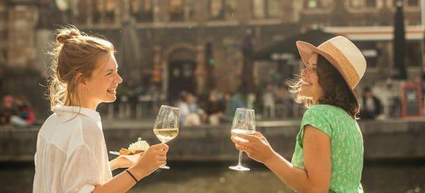 Twee jonge vrouwen die een glas wijn drinken